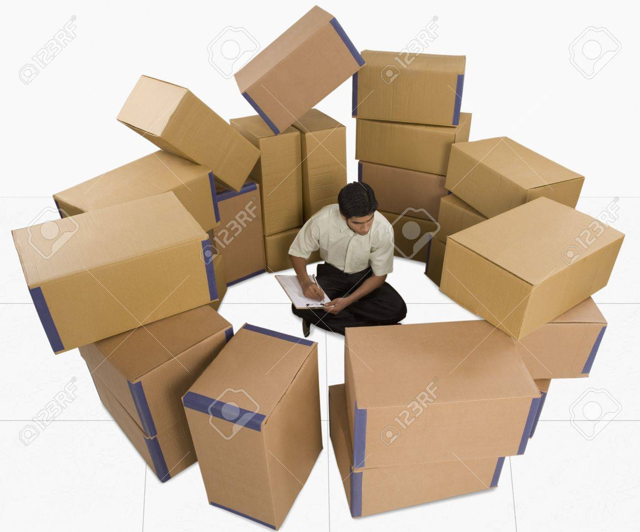 Store incharge sitting with cardboard boxes checking inventory Stock Photo - 10168454