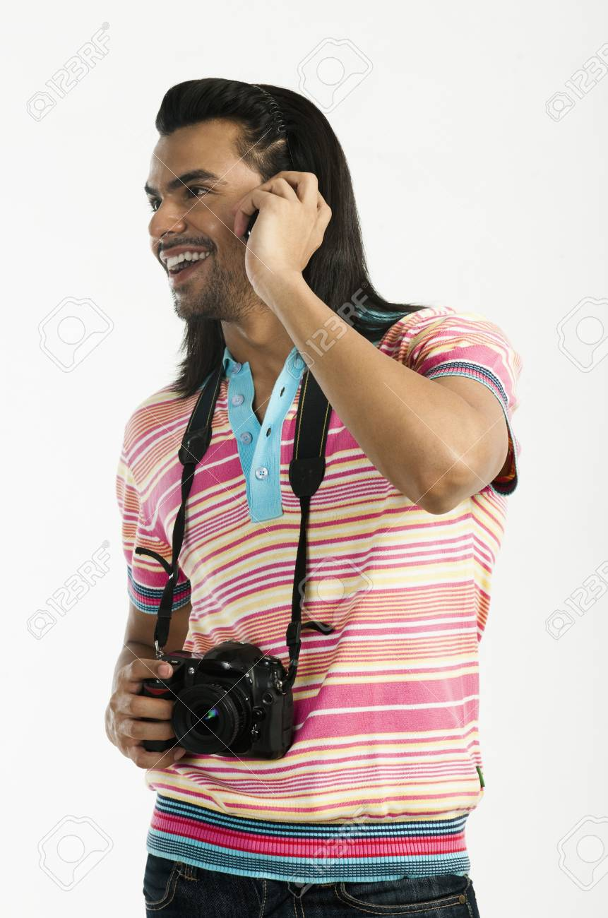 Photographer holding a digital camera and talking on a mobile phone Stock Photo - 10167838