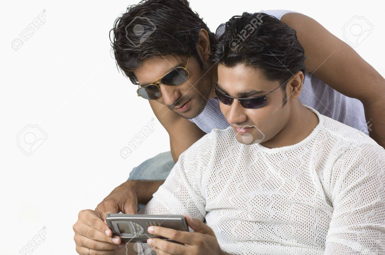 Two friends text messaging on a mobile phone Stock Photo - 10206408
