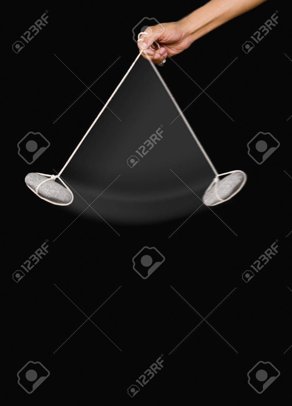 Close-up of a person's hand swinging a stone pendulum Stock Photo - 10241034