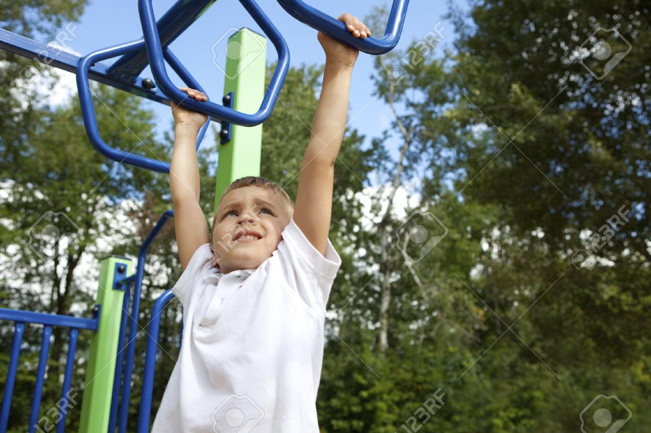 Boy playing on monkey bars Stock Photo - 10522476