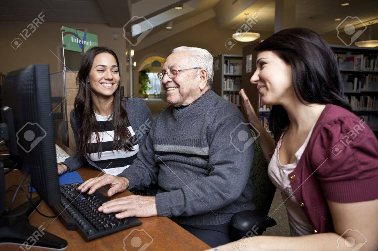 Volunteers teaching a senior how to use a computer Stock Photo - 10595302