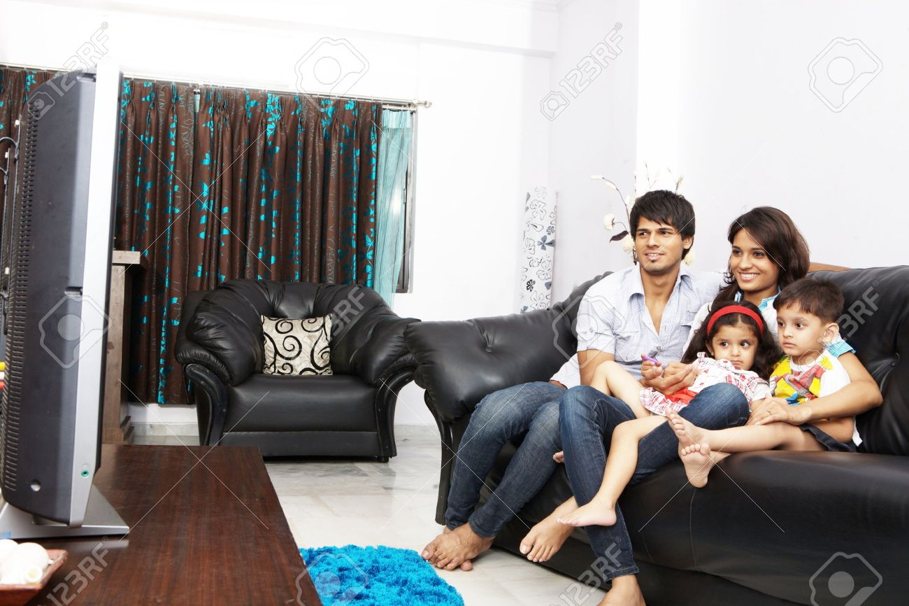 Family Watching Tv Together Sitting On A Sofa Stock Photo Picture