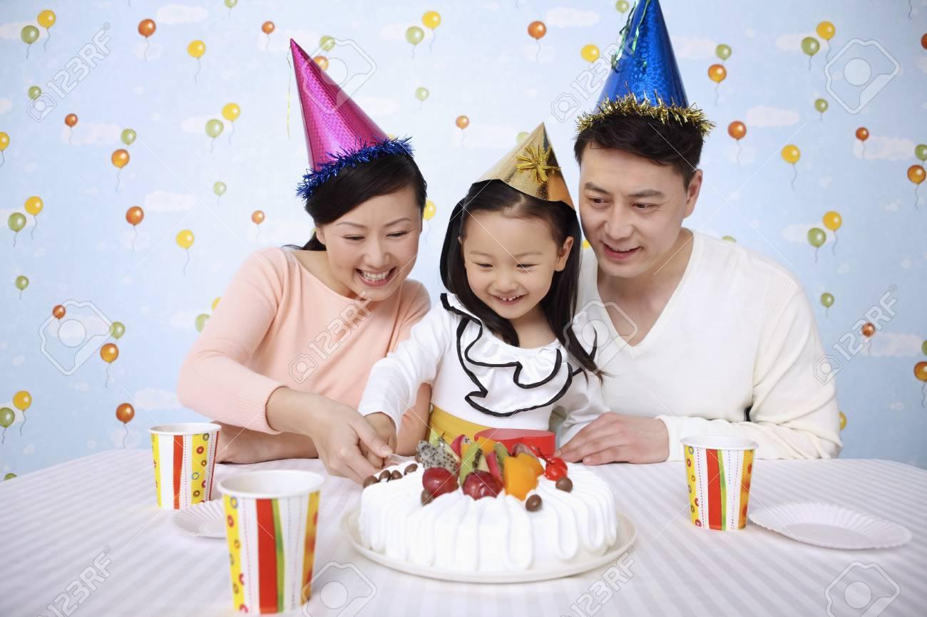 Mann Und Frau Die Geburtstagskuchen Mit Madchen Schneiden