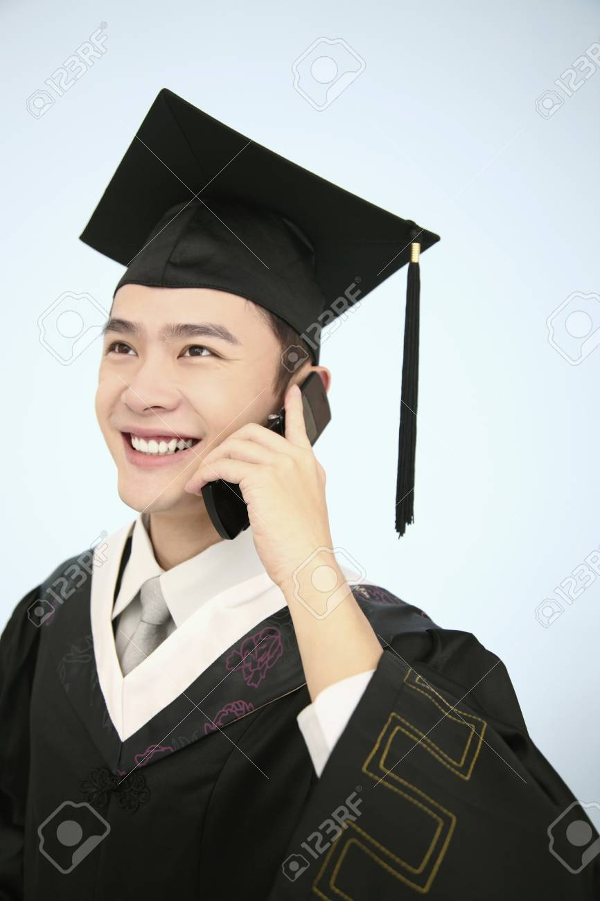 Man In Mortarboard And Graduation Gown Talking On The Phone Stock ...
