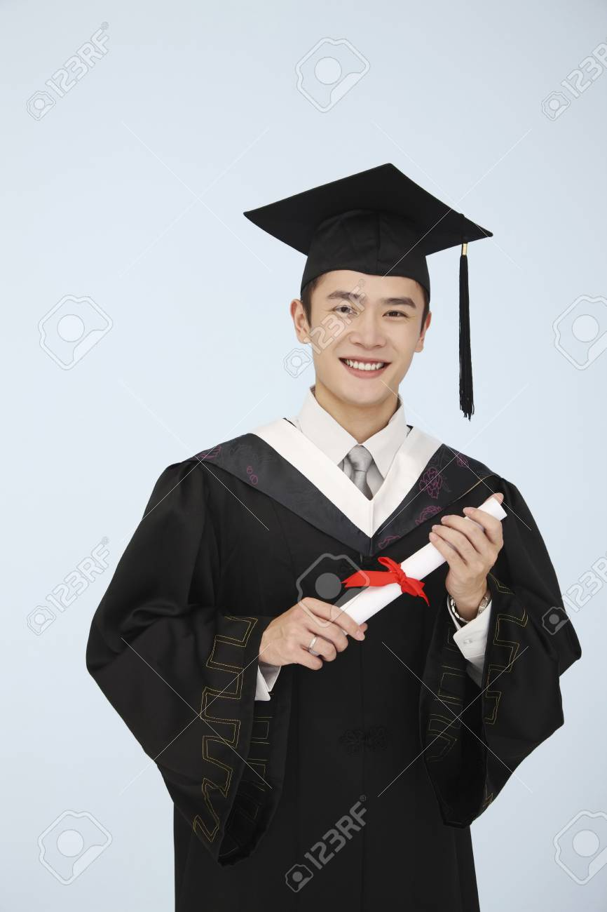 Man In Mortarboard And Graduation Gown Holding A Scroll Stock Photo ...