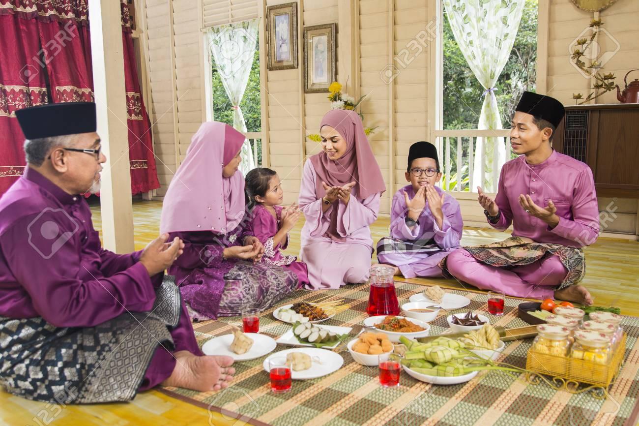 Muslim family saying prayers before meal - 120325482