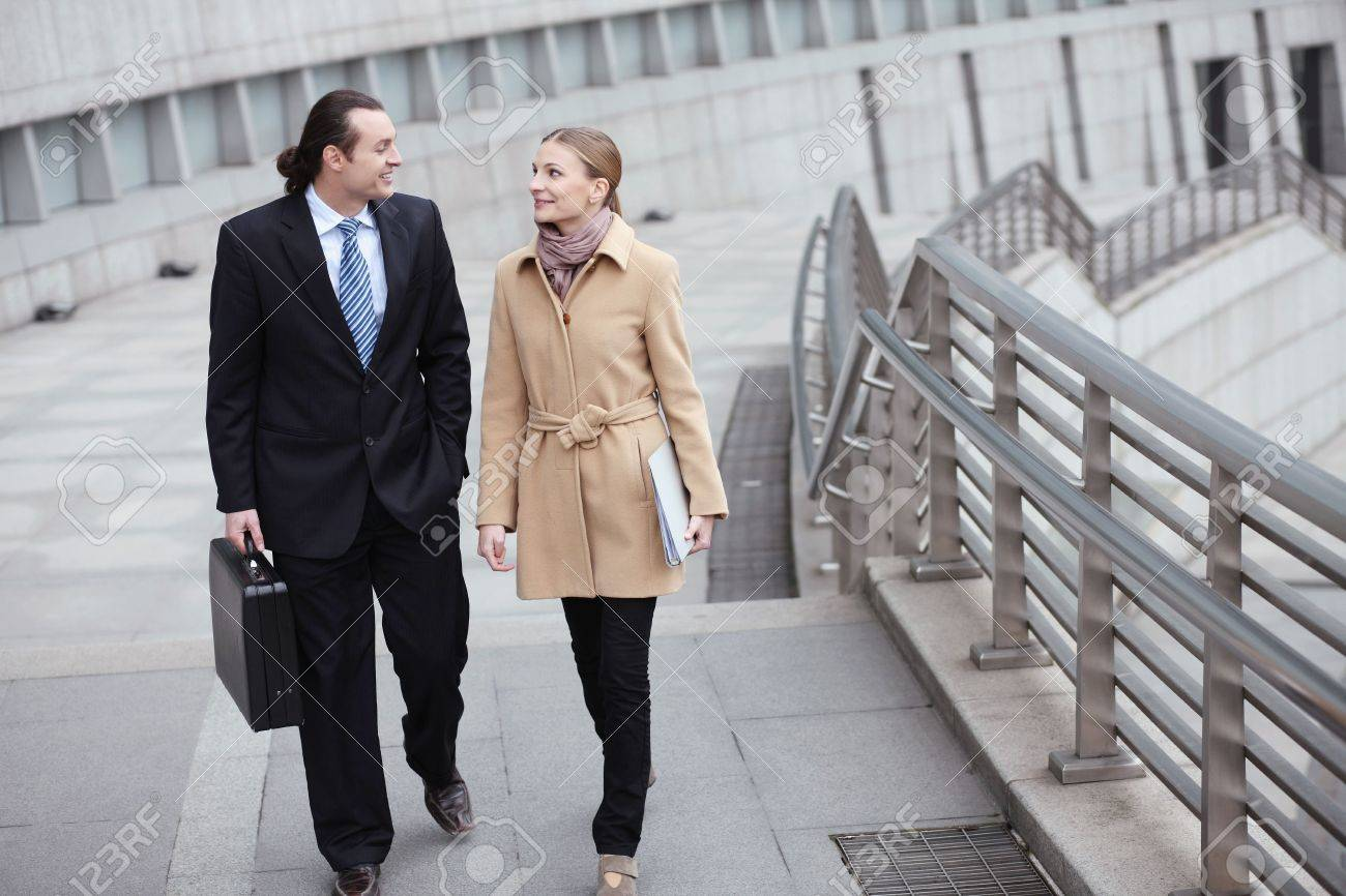 Businessman and businesswoman talking while walking Stock Photo - 6521117