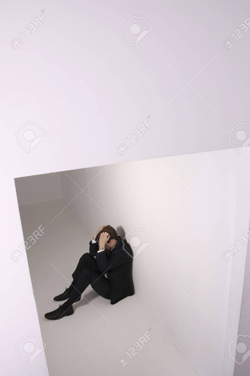 Man sitting on the floor wearing handcuffs with head in hands Stock Photo - 6546350