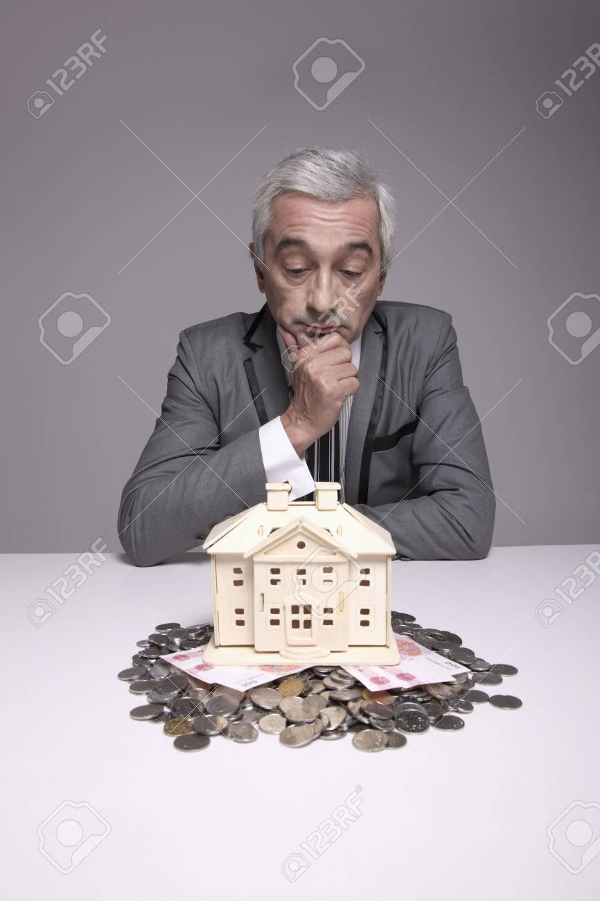 Businessman touching his chin while looking at wooden house model Stock Photo - 6581173