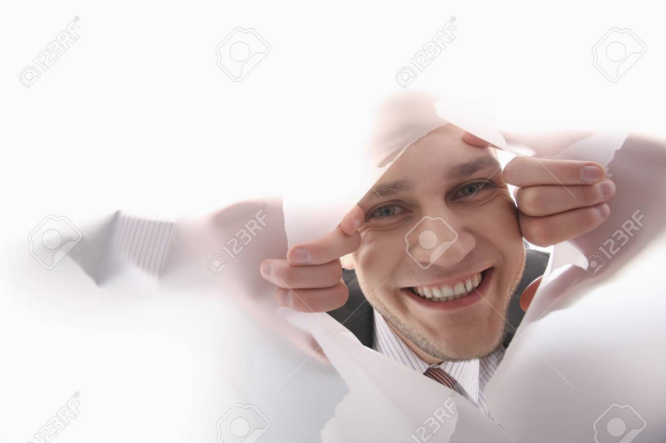 Businessman peeping through a hole torn in paper Stock Photo - 6866662