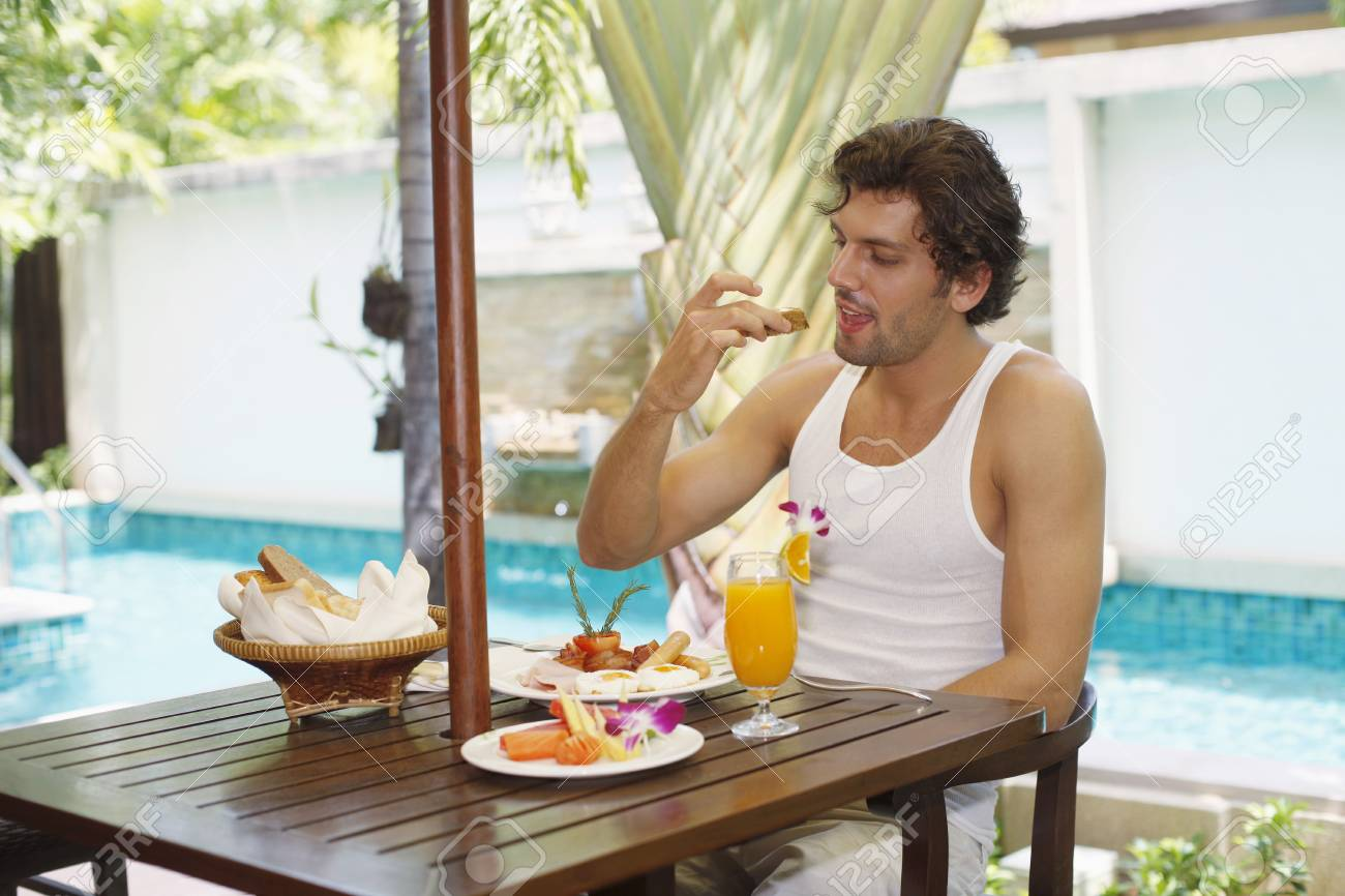 Man having breakfast by the pool Stock Photo - 6974156