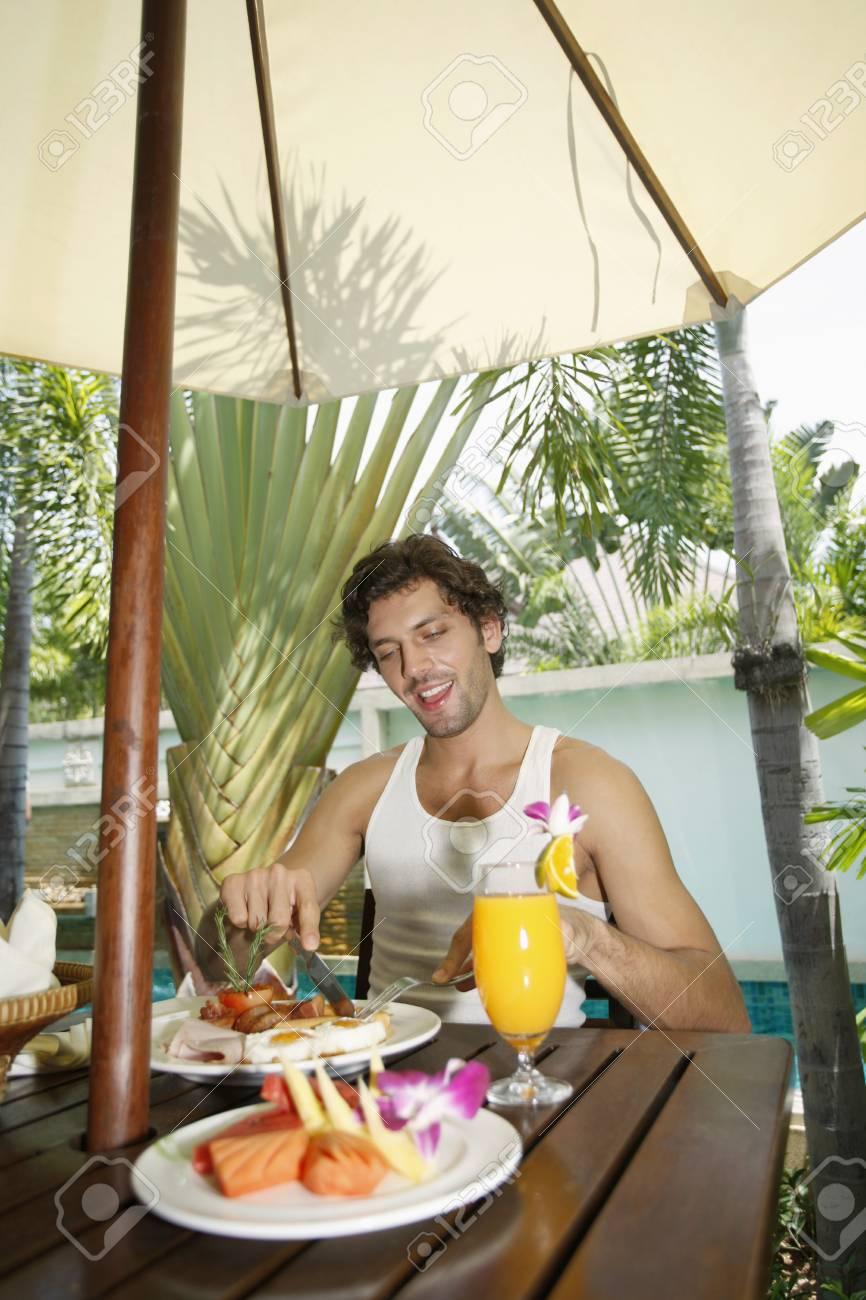 Man having breakfast by the pool Stock Photo - 6974157