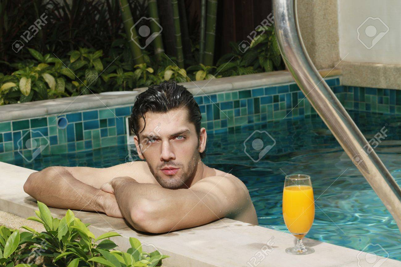 Man resting at the edge of the pool with a glass of orange juice at the side Stock Photo - 6974245