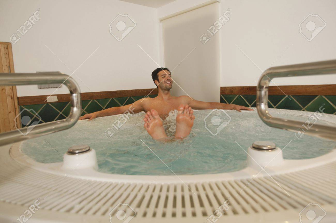 Man Relaxing In Hot Tub With Feet Showing From Water Surface Stock ...