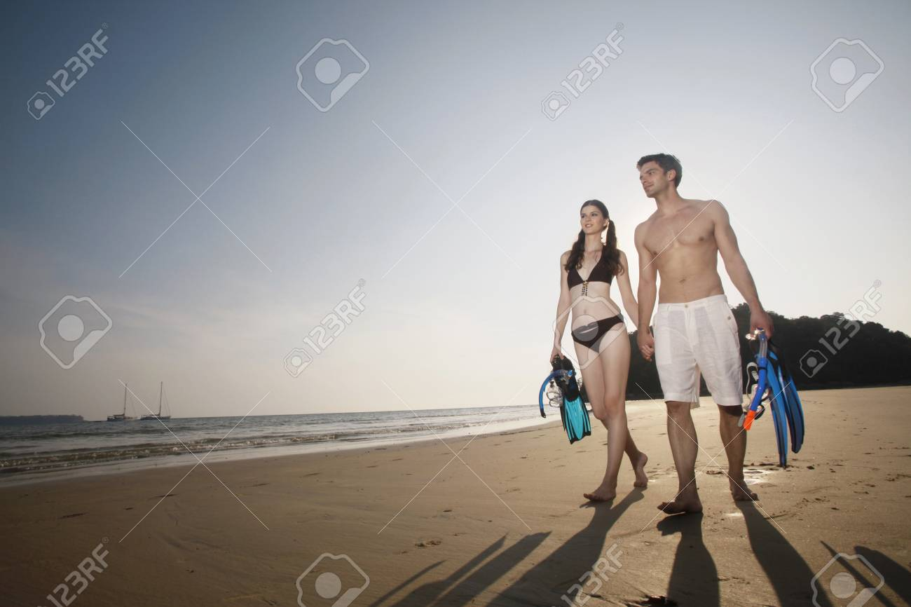 Man and woman carrying snorkeling gear Stock Photo - 7076988