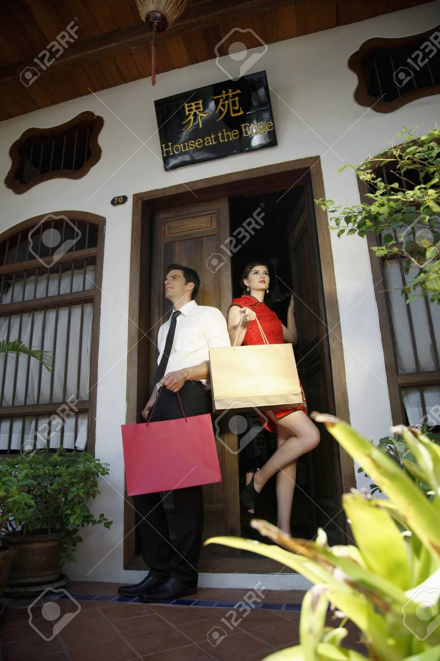 Man and woman with shopping bags standing at the doorway Stock Photo - 7131712