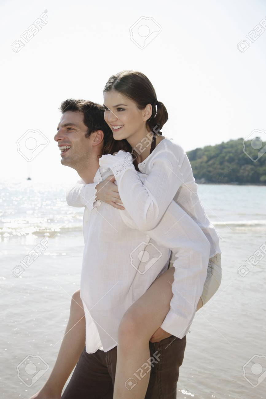 Man giving woman a piggy back ride on beach Stock Photo - 7355833