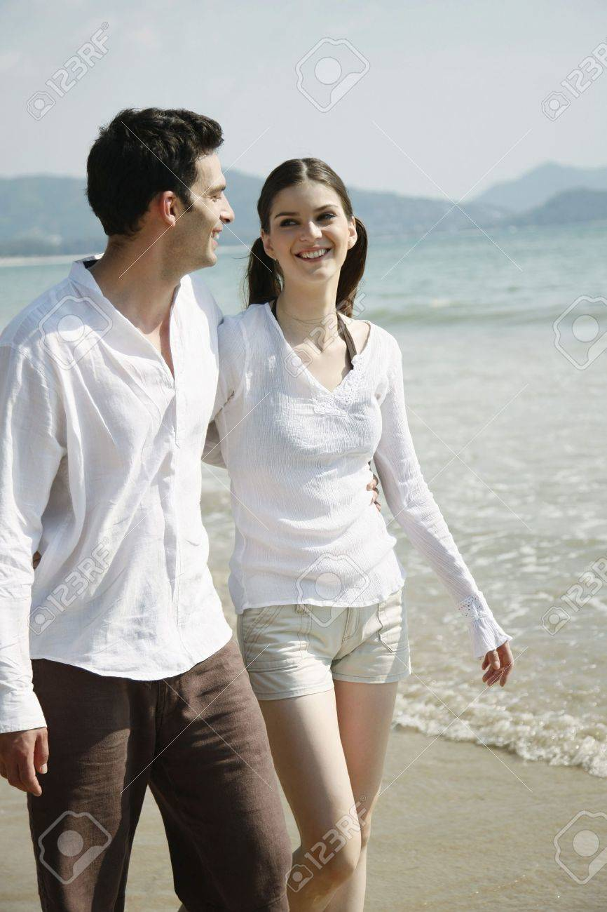 Man and woman walking along the beach Stock Photo - 7356052