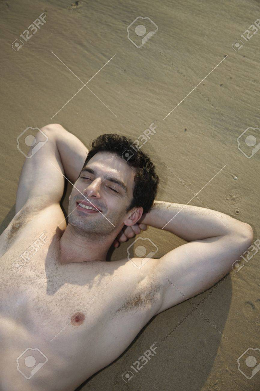 Man with bare chest lying down with eyes closed and hands behind head on beach Stock Photo - 7356163