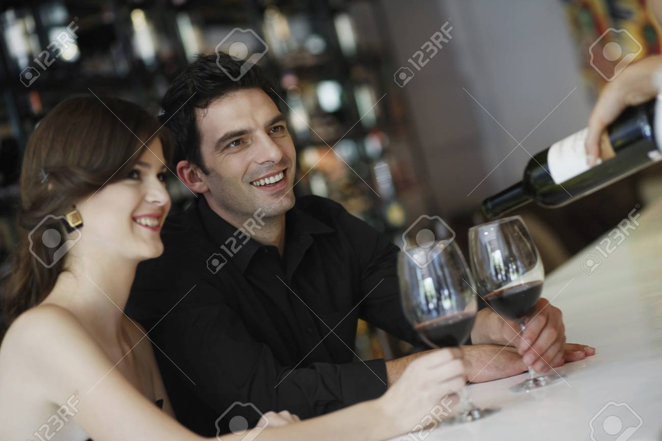 Man and woman having their glasses filled up Stock Photo - 7360833