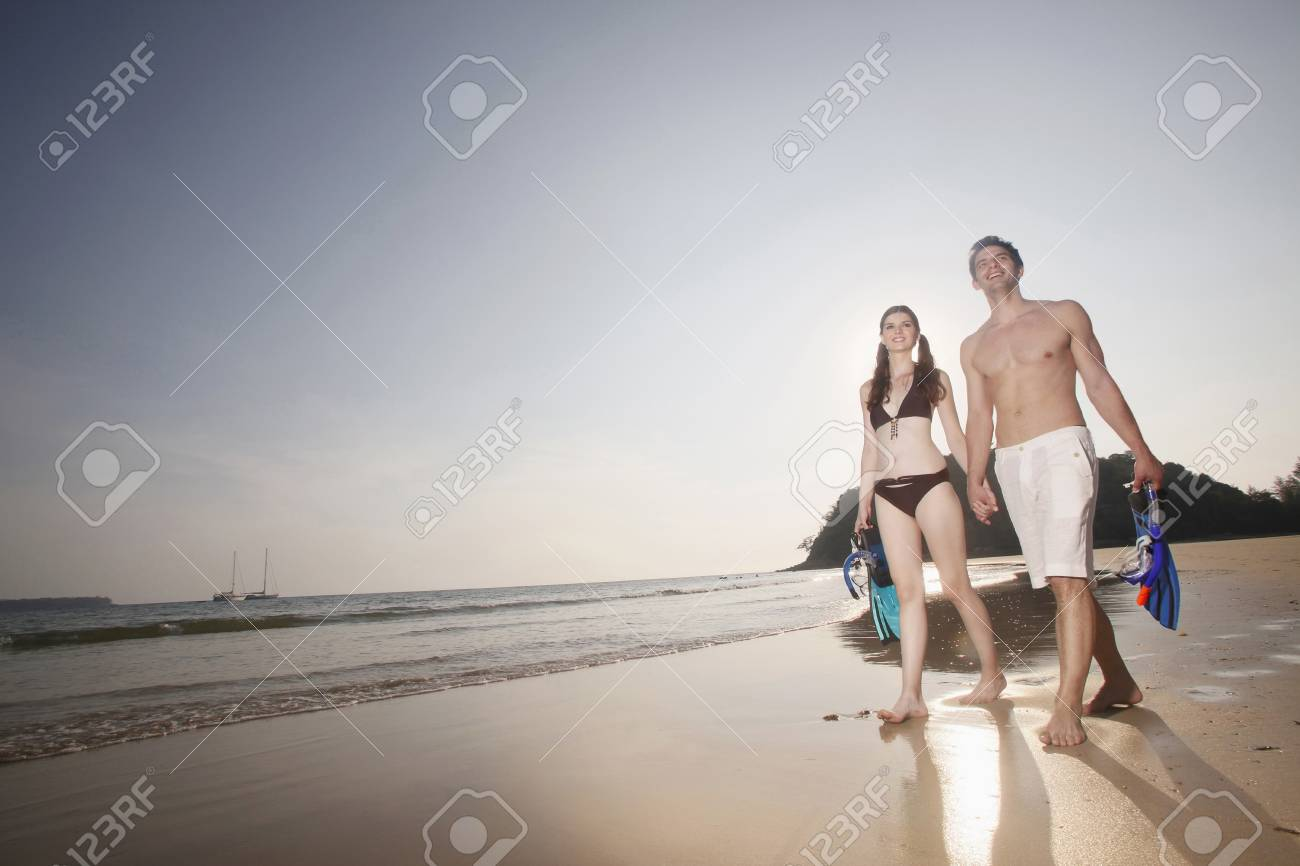 Man and woman carrying snorkeling gear Stock Photo - 7360803