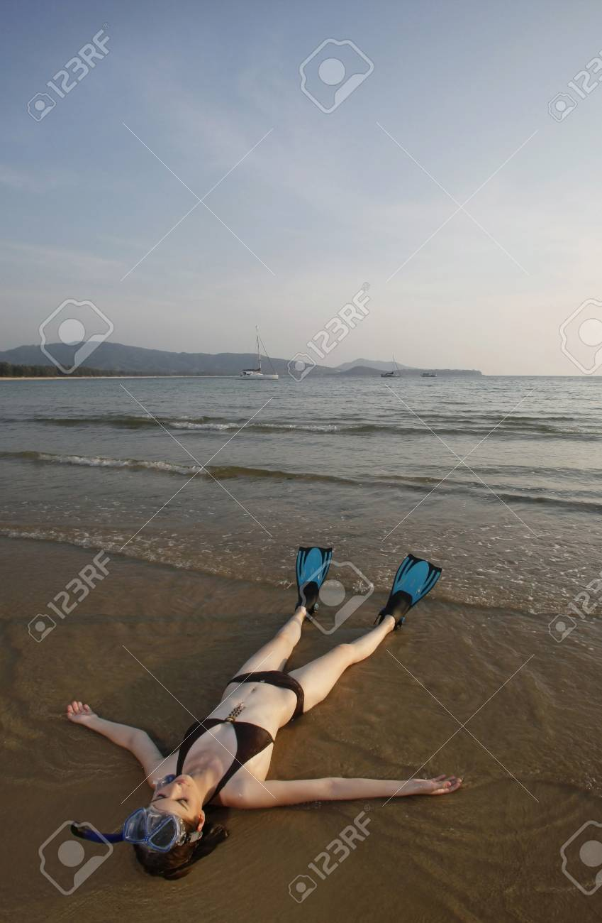 Woman with snorkeling gear lying on the beach Stock Photo - 7360807