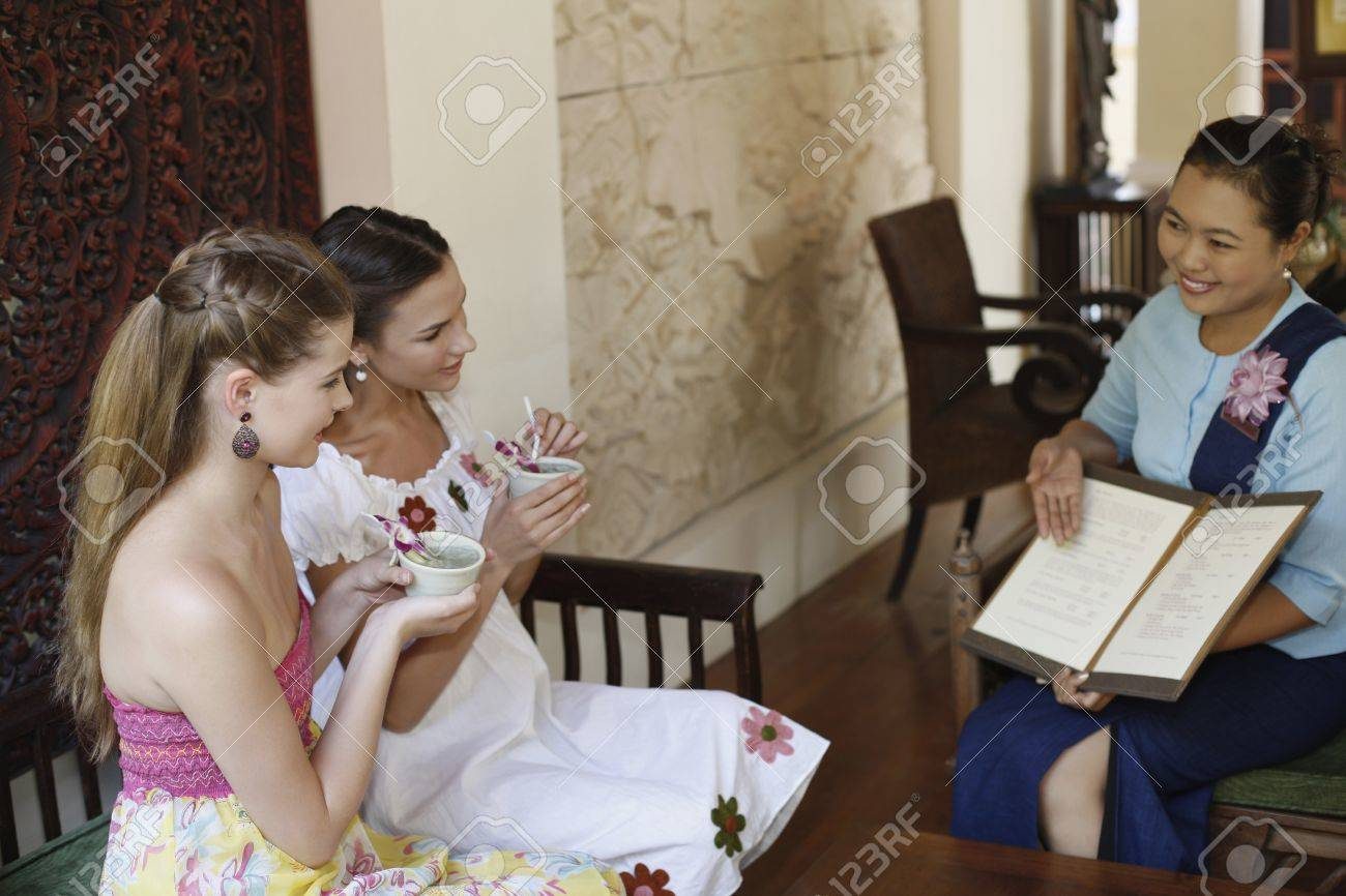 Customer service representative explaining about choices of spa while women enjoy their tea Stock Photo - 7360838
