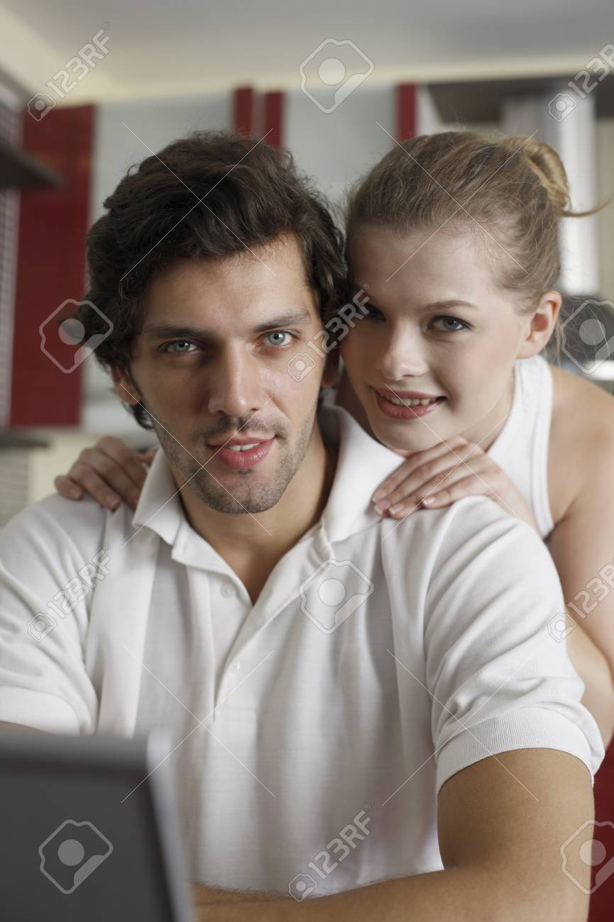 Woman standing behind man while he uses laptop Stock Photo - 7360470
