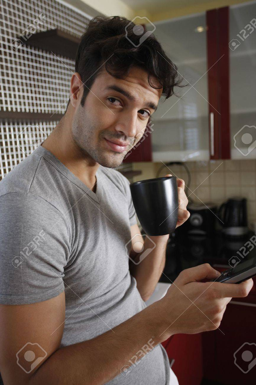 Man enjoying a cup of coffee while text messaging Stock Photo - 7360978