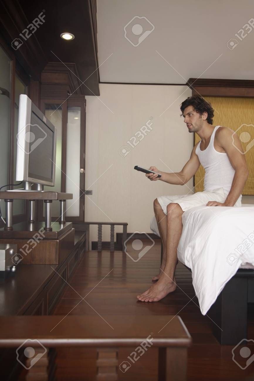 Man with remote control in hand watching television Stock Photo - 7360457