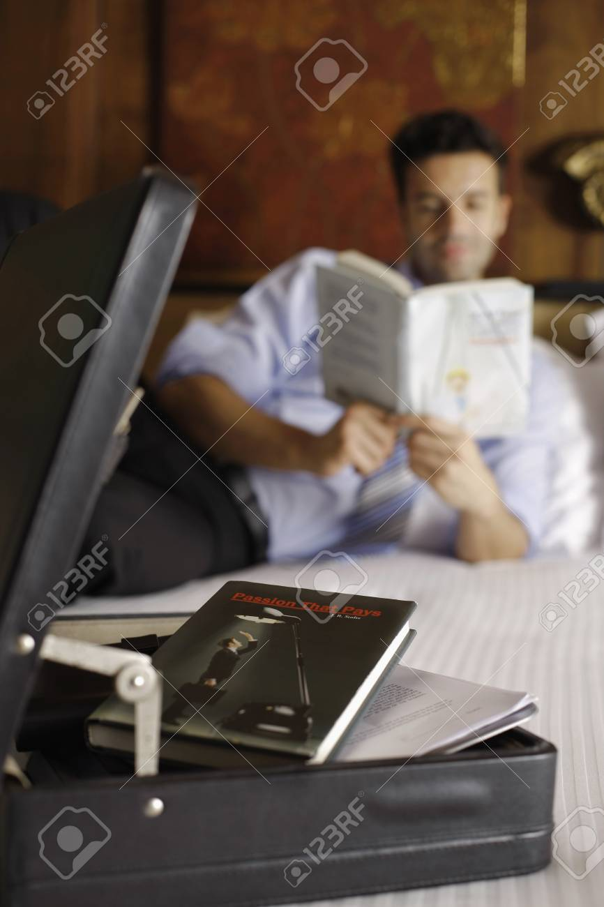 Businessman reading book on bed, focus on briefcase Stock Photo - 7359016