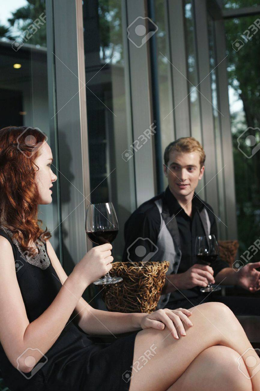 Man and woman holding glasses of red wine while chatting Stock Photo - 7362470