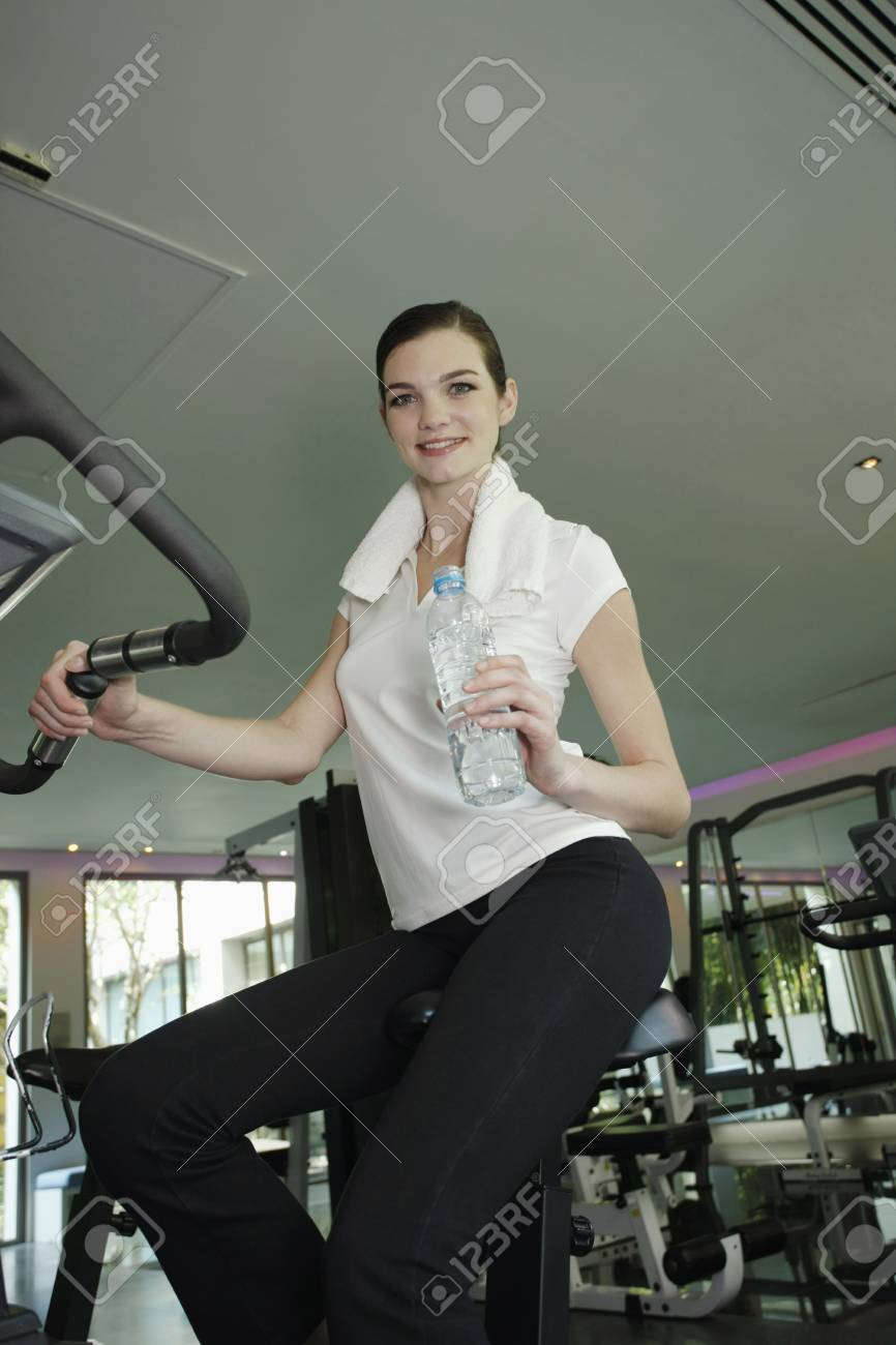 Woman holding a bottle of water while exercising in the gymnasium Stock Photo - 7446283