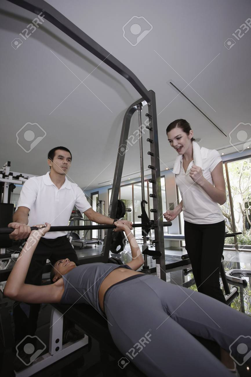 Personal trainer helping woman exercising in gymnasium, friend giving support Stock Photo - 7446569
