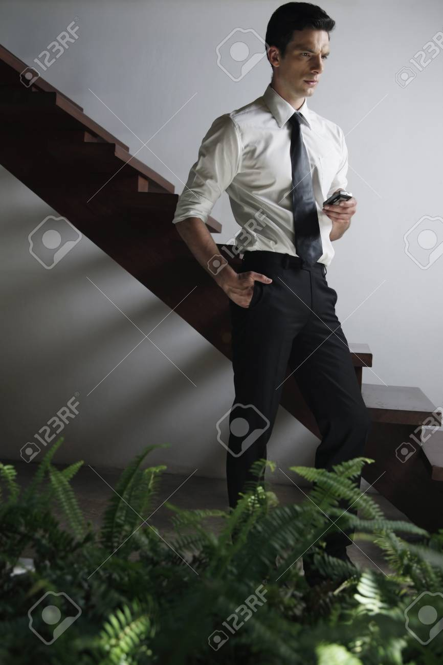 Businessman with mobile phone contemplating Stock Photo - 7445803