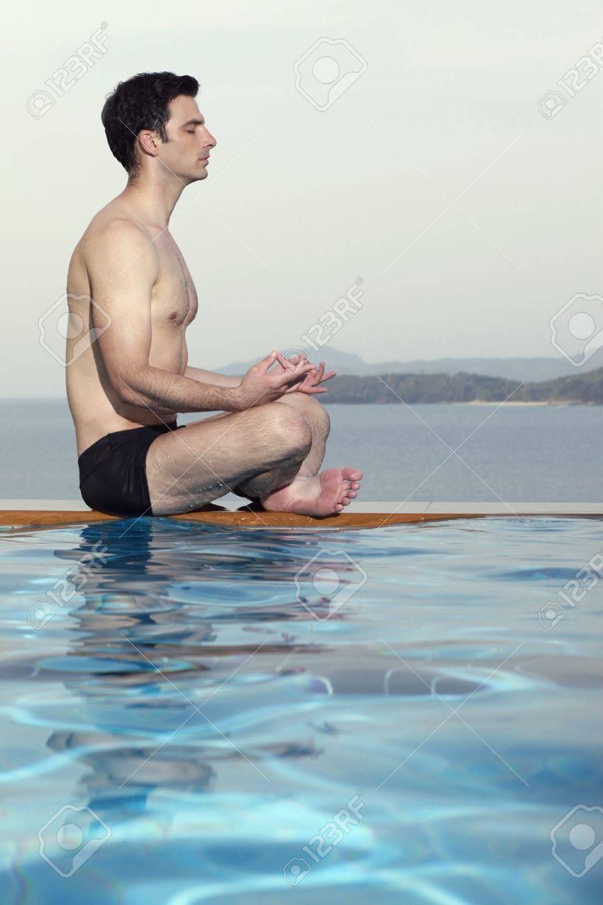 Man meditating by edge of swimming pool Stock Photo - 7446451