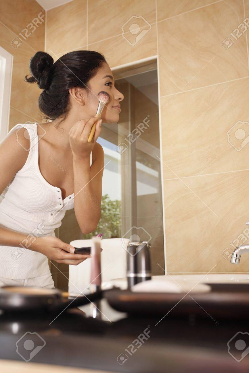 Woman applying makeup in the bathroom Stock Photo - 7446445