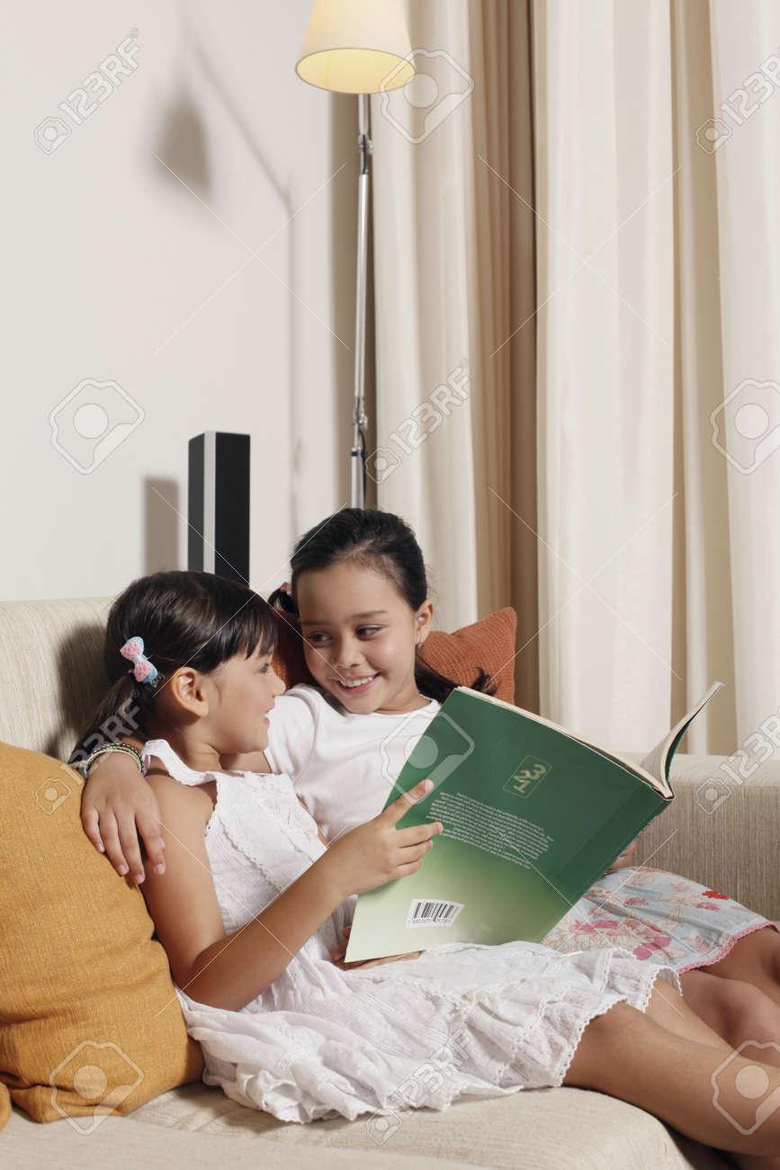 Girls reading together on sofa Stock Photo - 7446472