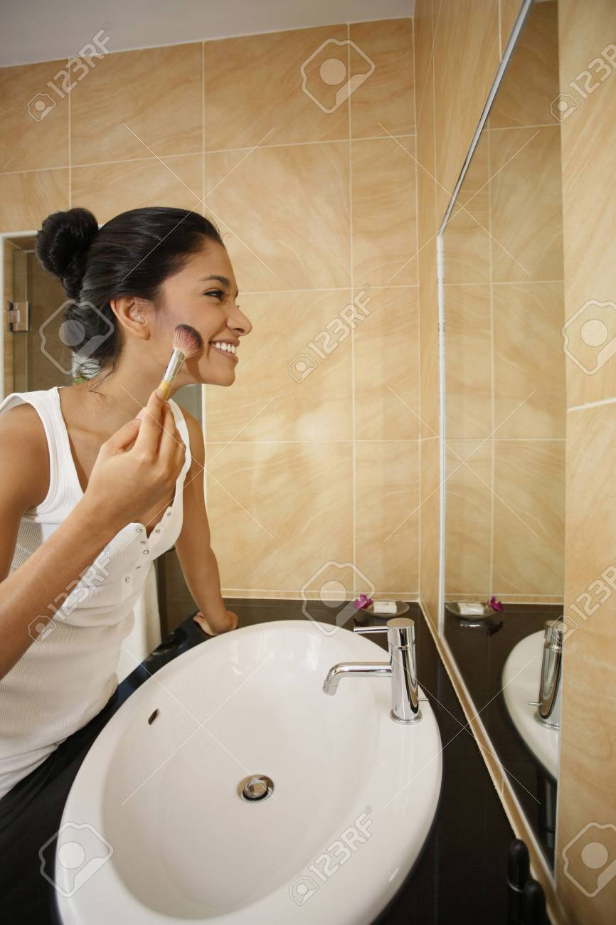 Woman applying makeup in the bathroom Stock Photo - 7470619