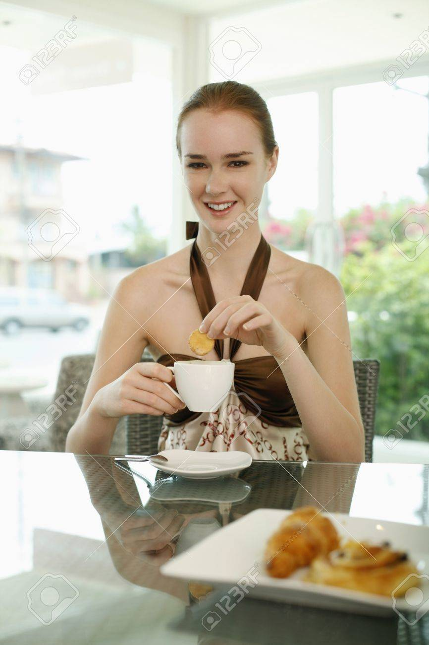 Woman dipping biscotti into coffee Stock Photo - 7534458