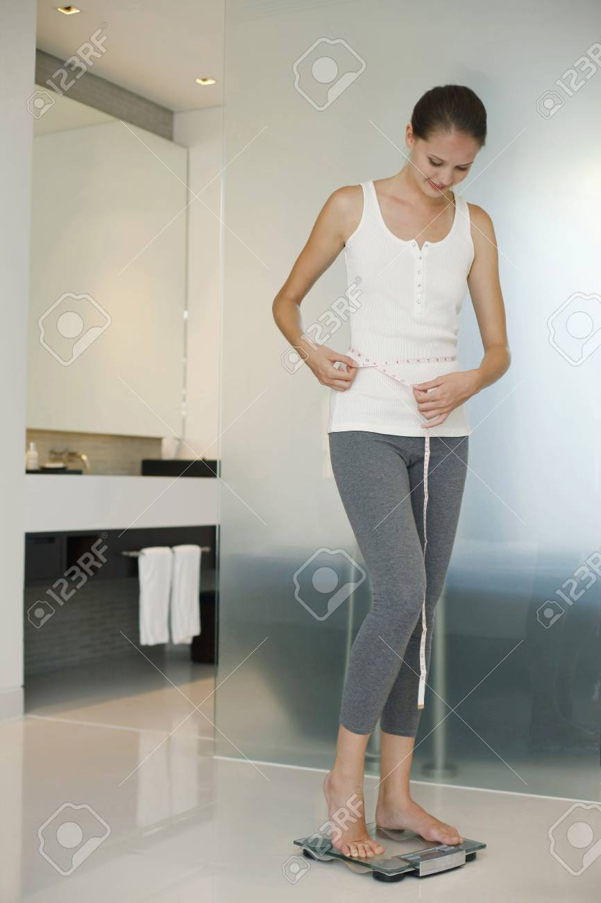 Woman standing on weight scale and measuring her waist Stock Photo - 7534649