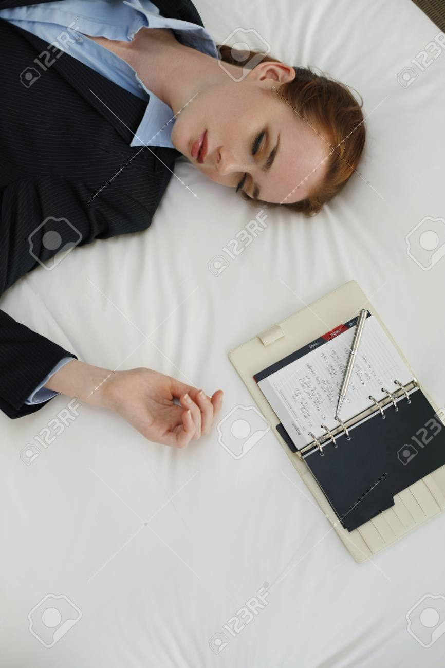 Businesswoman lying down on bed with organizer beside her Stock Photo - 7534693