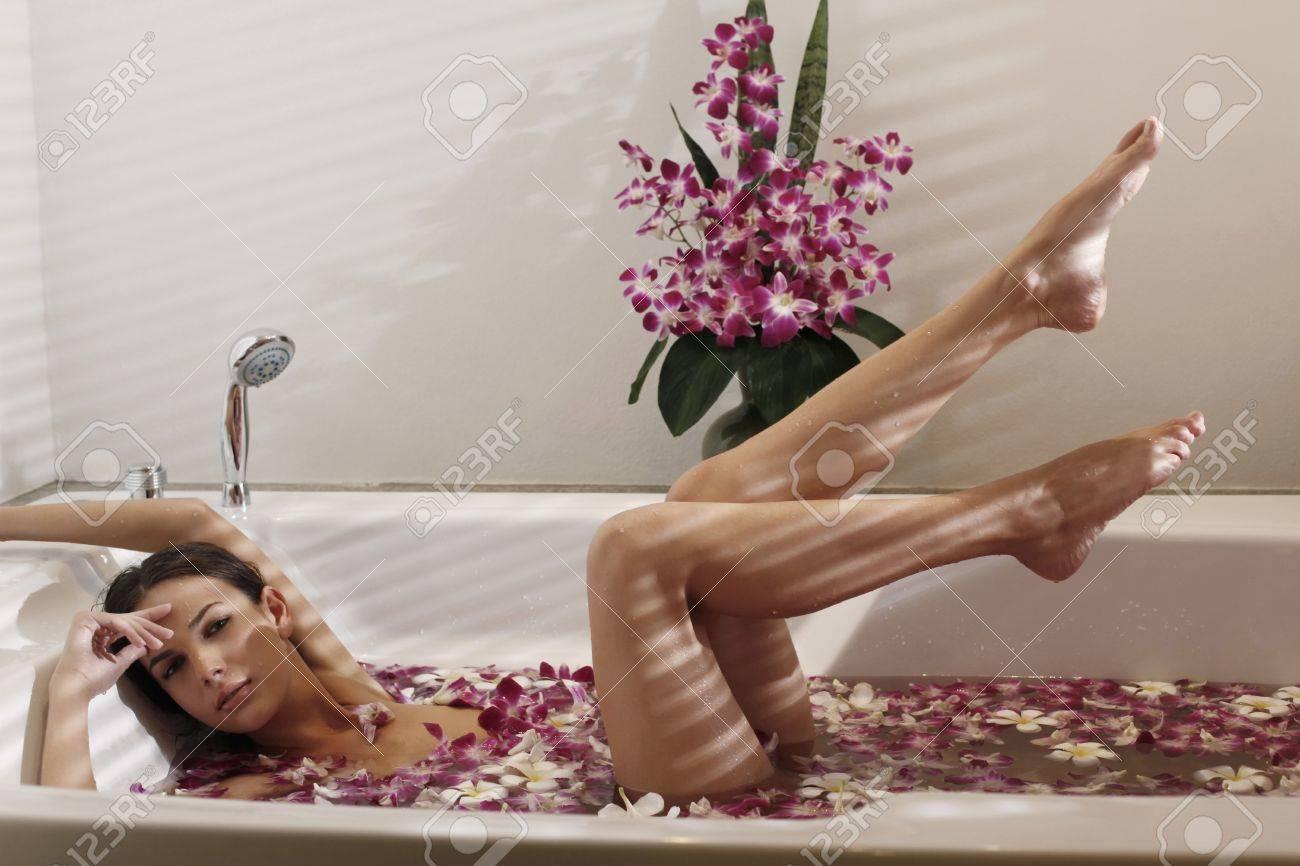 archivio fotografico donna relax nella vasca da bagno con petali di fiori di sollevare le gambe