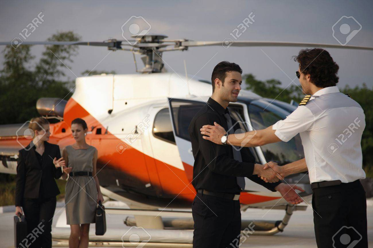 Businessmen shaking hands while businesswomen are walking from helicopter in the background Stock Photo - 7594863