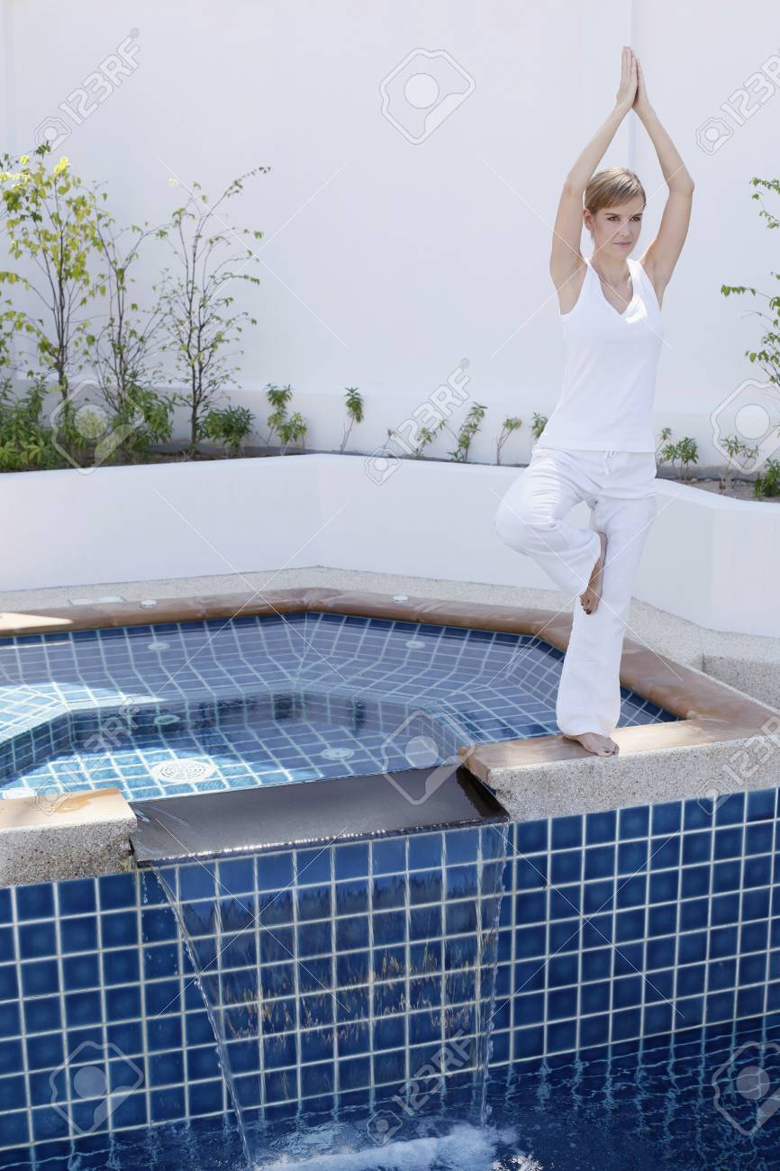 Woman practising yoga by the pool side Stock Photo - 7595687