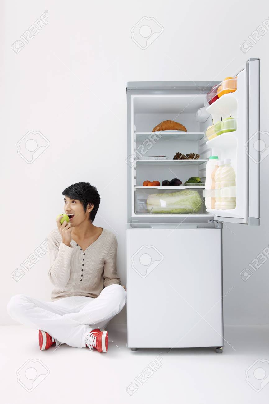 Man sitting next to refrigerator, eating green apple Stock Photo - 7643754