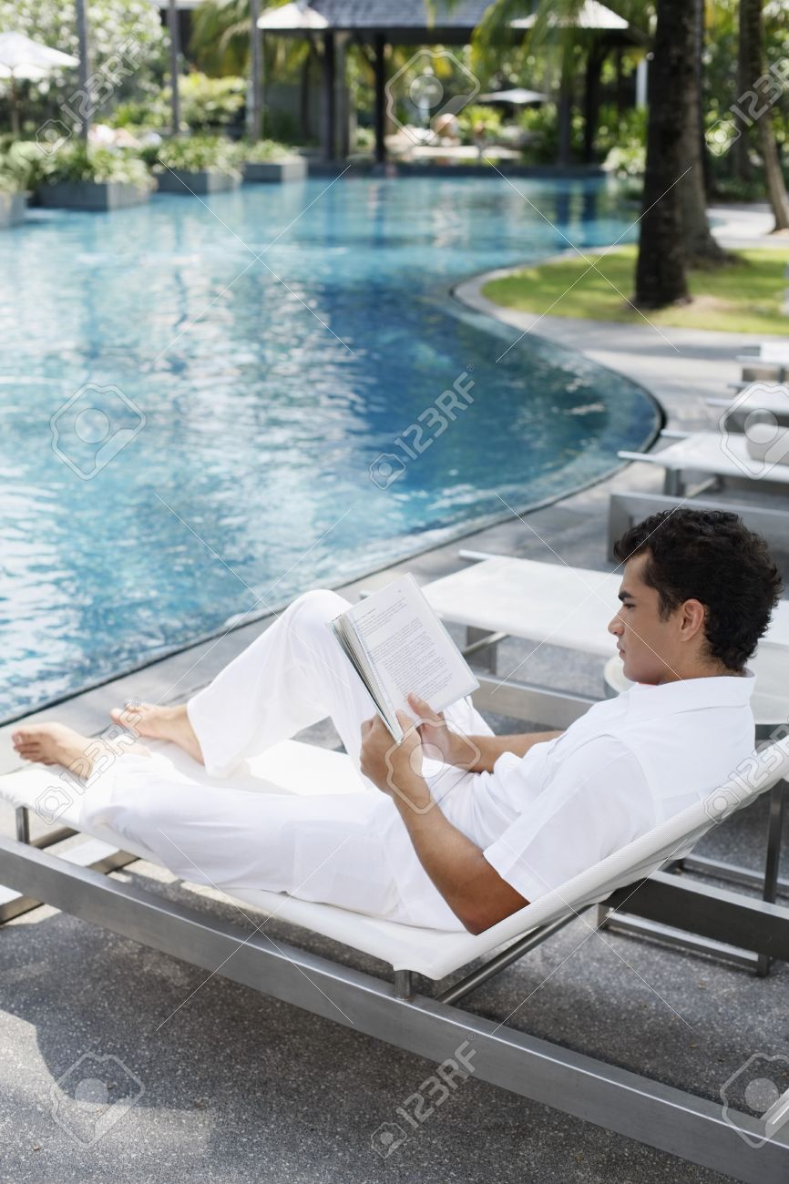 Man sitting on lounge chair reading book Stock Photo - 7644200