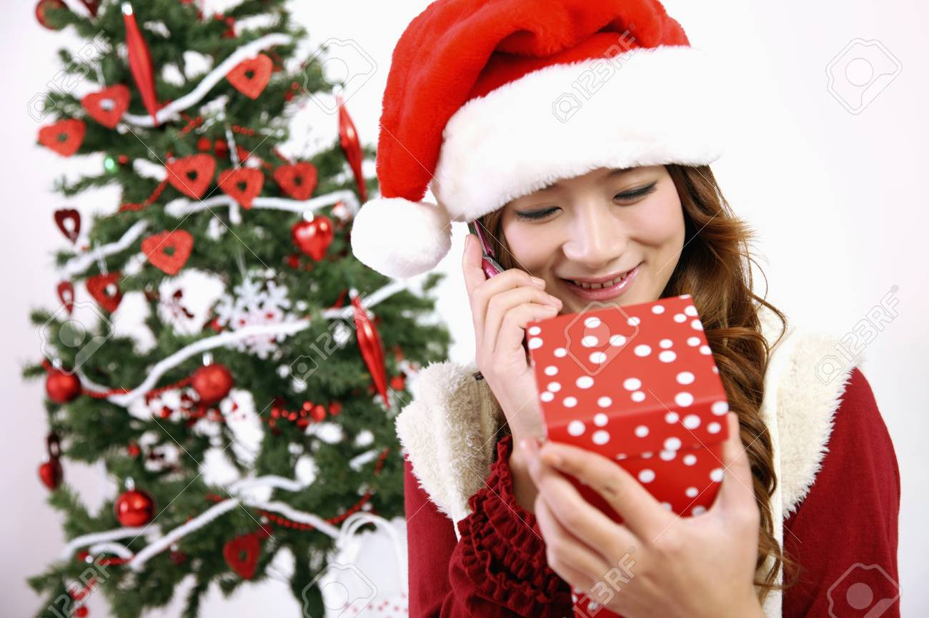 Woman talking on the phone while looking at gift box Stock Photo - 8148846