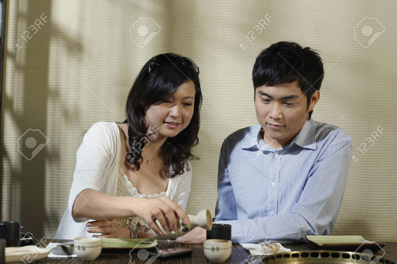 Woman pouring sake into man's cup Stock Photo - 8149084